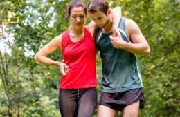Image of male runner helping a female runner who is limping